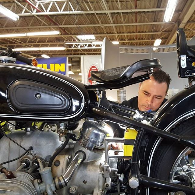 Matt McGinn working to remove engine from two wheeled BMW